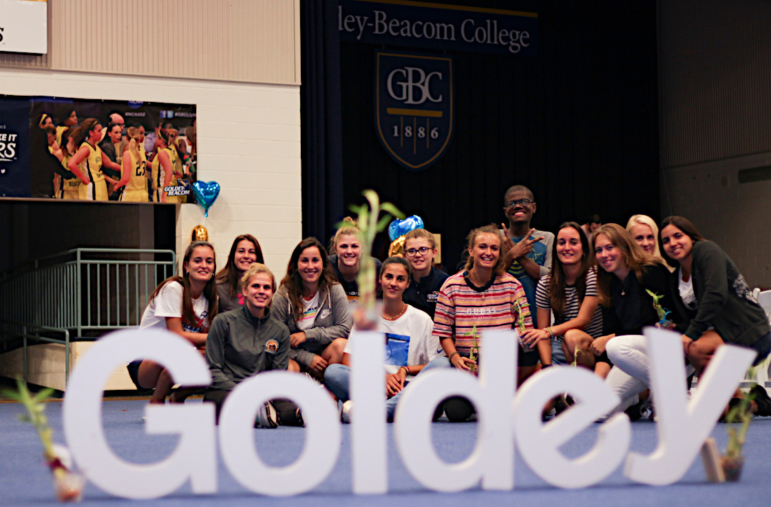 Students behind white Goldey sign